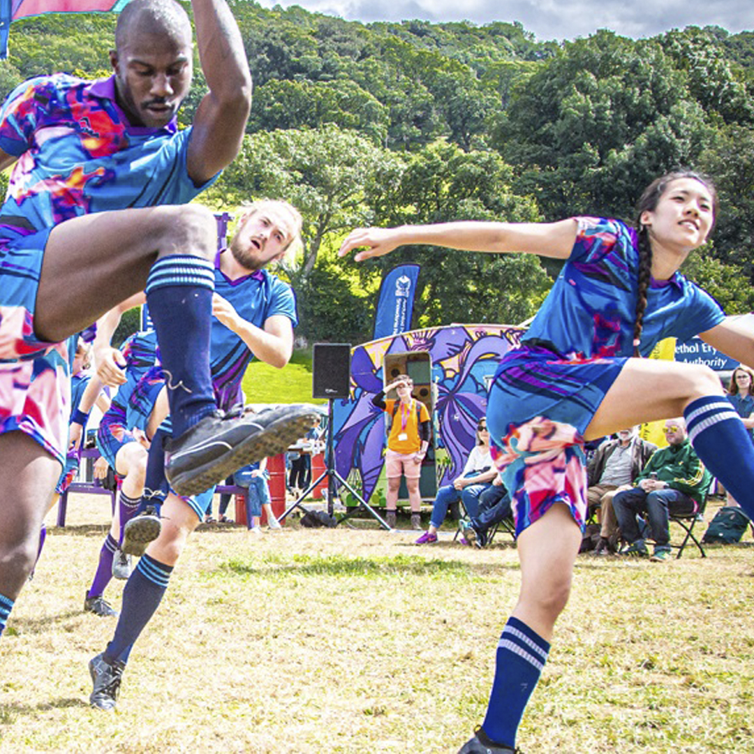 dancers in rugby kit smiling and kicking high