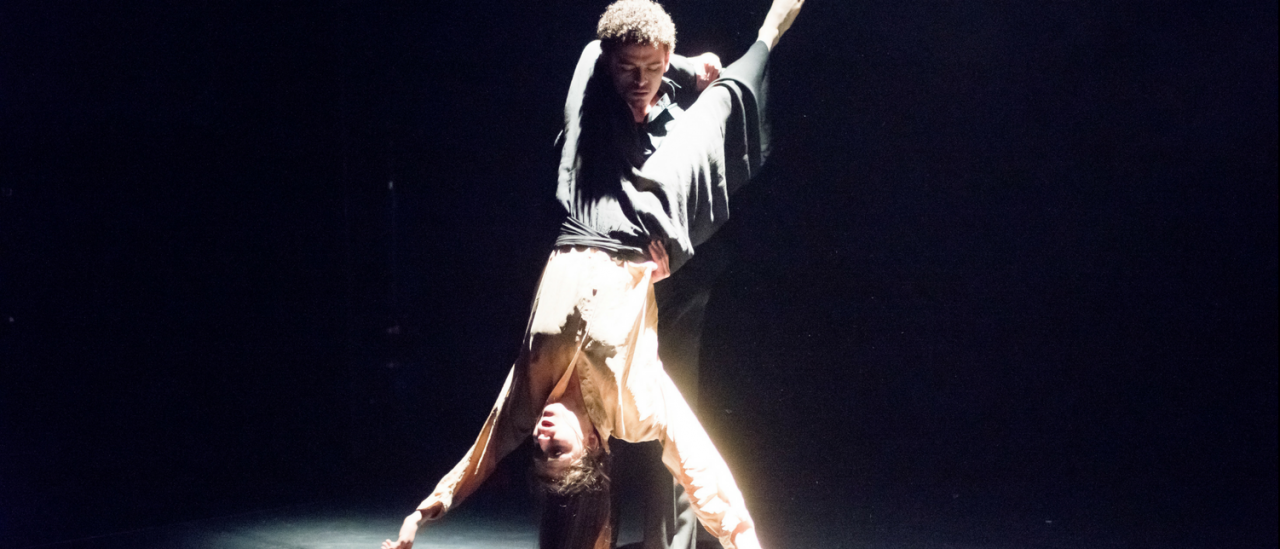 Cyril performing in Ecrit, holding dancer around his back