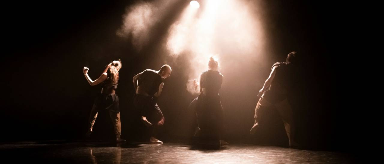 Atalay dancers facing the back with dust in the air