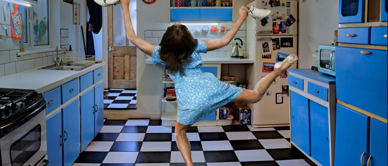 Roots, blue kitchen with dancer facing the back, legs in the air
