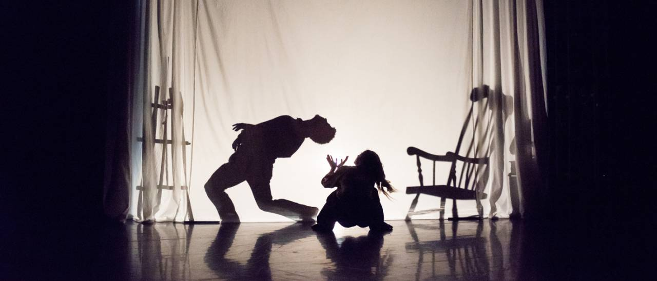 2 dancers, one as a silhouette behind a sheet and the second looking up from the floor