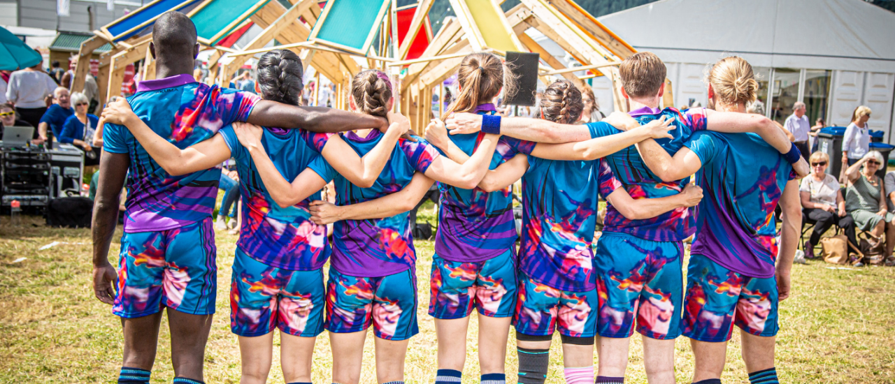 dancers in rugby kit standing with their arms around one another