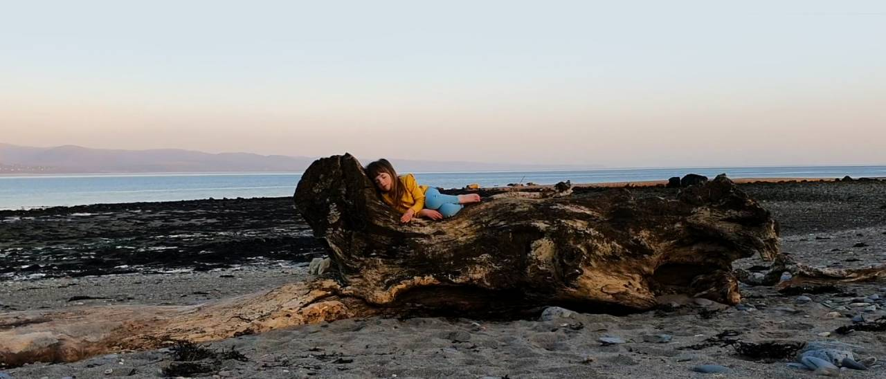 a young girl lying on a piece of driftwood