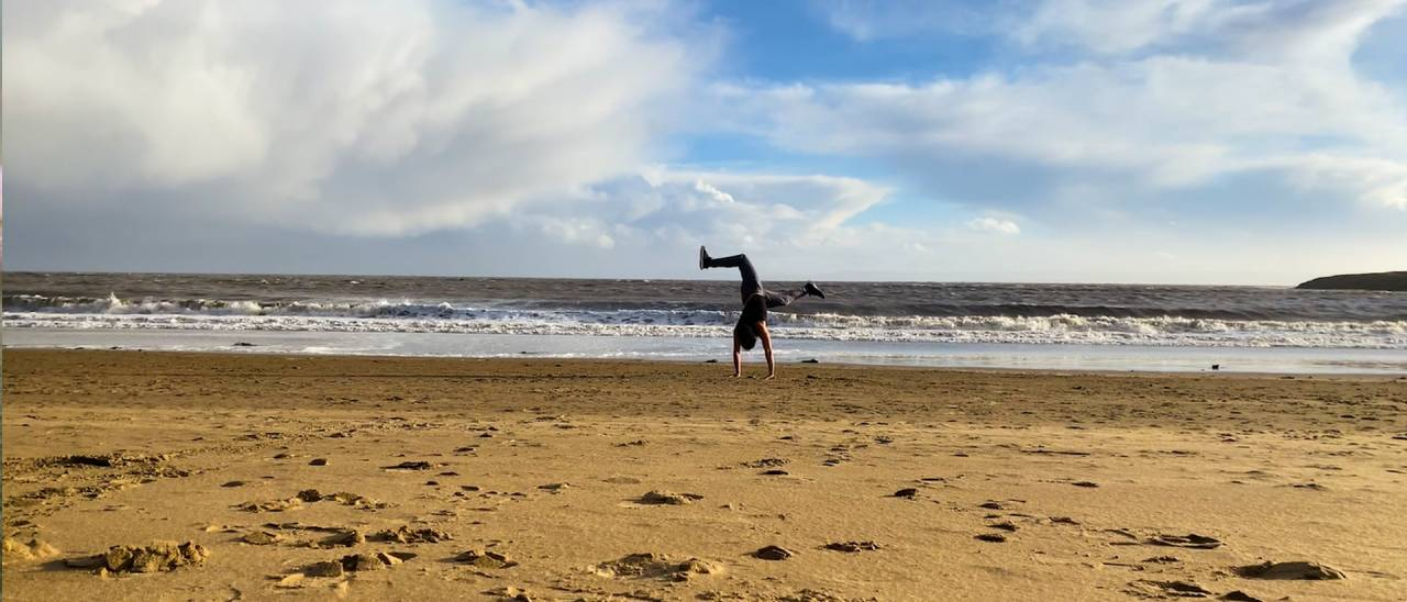 image of dancer doing a headstand on the beach