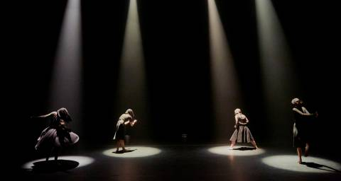 4 dancers each under a spotlight dressed in black