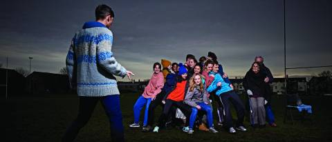Fearghus directing a group in a huddle on a rugby pitch