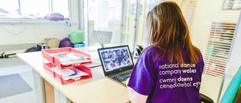 Puple t-shirt, brown medium length hair down, logo on the back of t-shirt looking at a computer screen