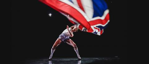 Male dancer in heels and stockings waving a British flag above his head