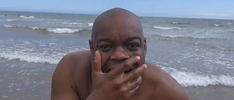 Marvin standing with hand over mouth, sea behind him