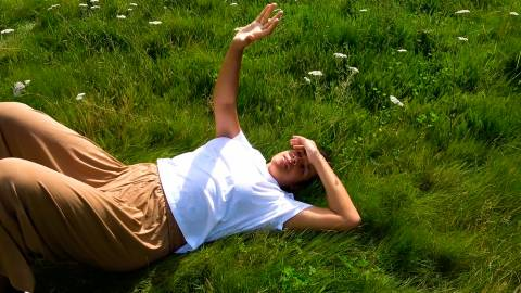 Shakeera lying in a green field with her hand towards the sun