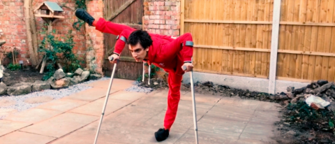 Joe, a young male dancer in red clothes dances in his back yard using crutches whilst it holds his leg up at a 90 degree angle